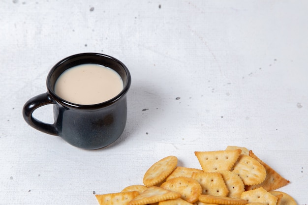 Вид спереди чашки молока с крекерами на светлой поверхности