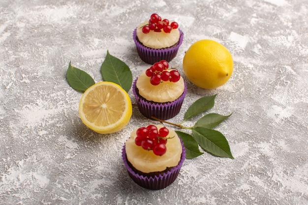 Вид спереди вкусные пирожные со свежими лимонами на светлой поверхности