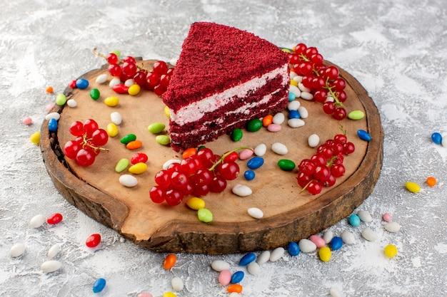 カラフルなキャンディーの木製の机の上のクリームとフルーツのおいしいケーキスライスの正面図
