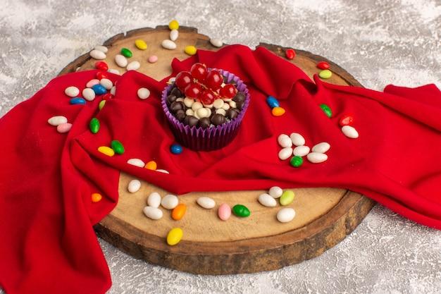 明るいライトデスクにキャンディーとおいしいチョコレートブラウニーの正面図