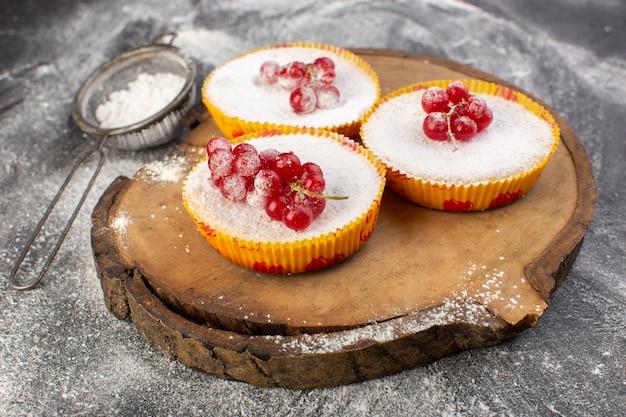 Вид спереди вкусные клюквенные пирожные с красной клюквой на верхней части кусочки сахара и порошок