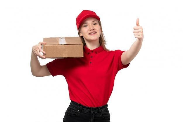 Вид спереди молодая женщина курьер работница службы доставки еды, улыбаясь, держа коробку доставки на белом