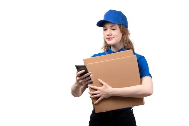 Вид спереди молодая женщина курьер работница службы доставки еды, улыбаясь, проведение доставки коробки на белом