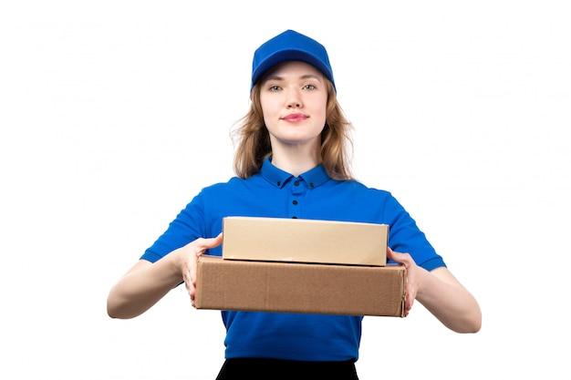 Вид спереди молодой курьер женского пола в синей рубашке синей кепке и черных брюках с коробками доставки на белом