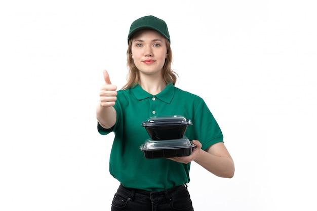 Вид спереди молодая женщина курьер в зеленой форме, держа миски с едой, улыбаясь на белом