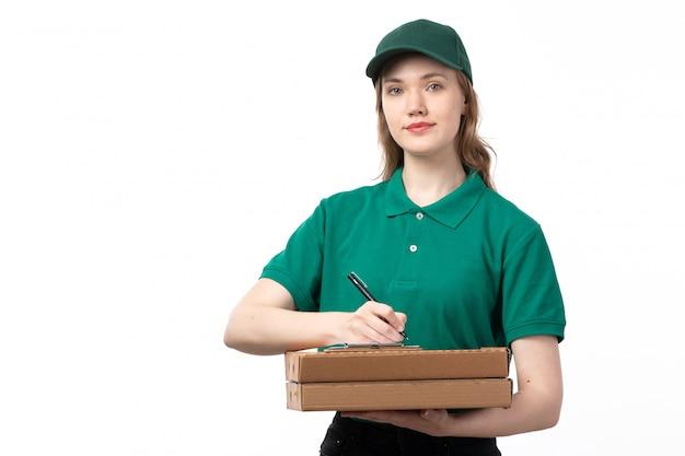白の新しい注文を書き留めるピザと緑の制服保持ボックスで正面の若い女性宅配便