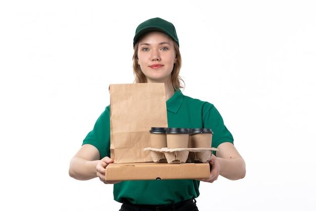 Вид спереди молодой женщины курьер в зеленой форме, держа чашки кофе и улыбается на белом