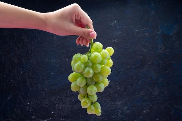 Вид спереди женщина держит виноград на темно-синем