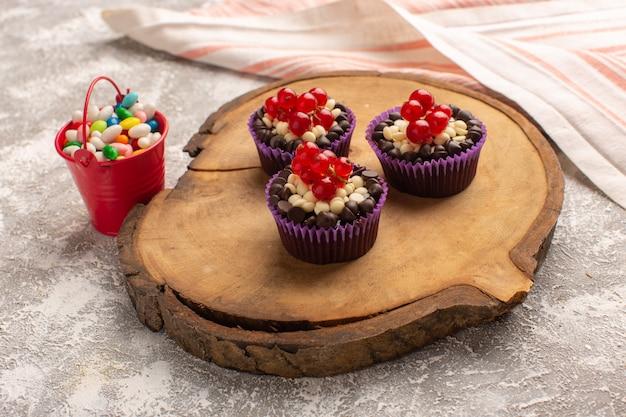 Вид спереди маленькие шоколадные пирожные с клюквой и конфетами на сером