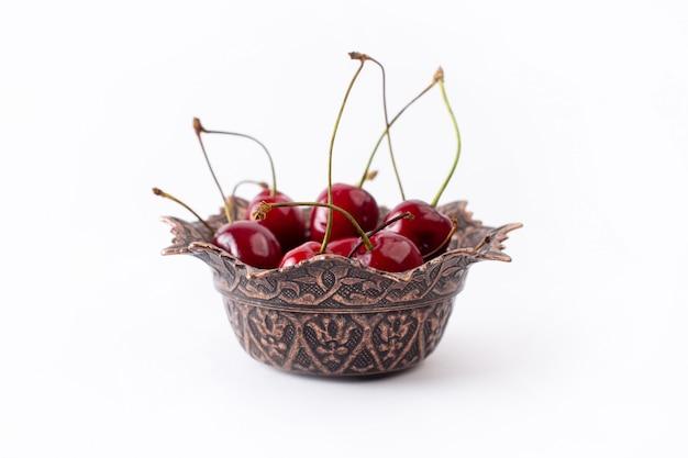 Красная вишня вид спереди внутри тарелки на белом