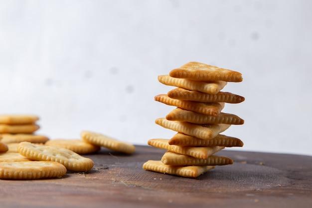 木製の机の上に並べられた塩味のおいしいポテトチップスと軽いクラッカーのぱりっとしたスナック