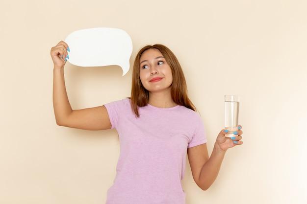 Вид спереди молодая привлекательная женщина в розовой футболке и синих джинсах, держащая стакан воды и белый знак