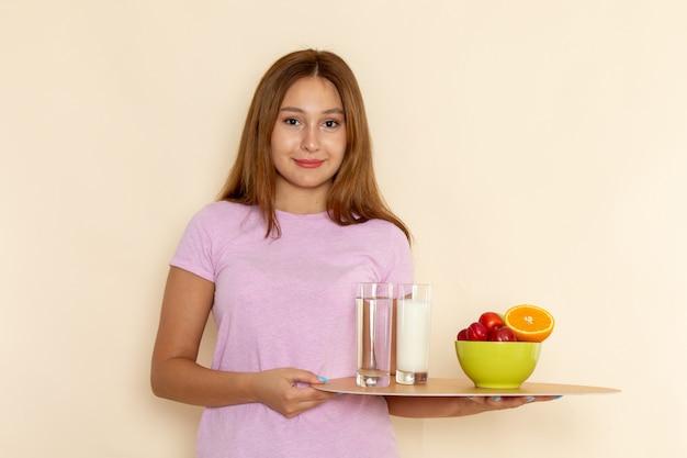 Вид спереди молодая женщина в розовой футболке и синих джинсах, держащая поднос с фруктами, молоком и водой на сером