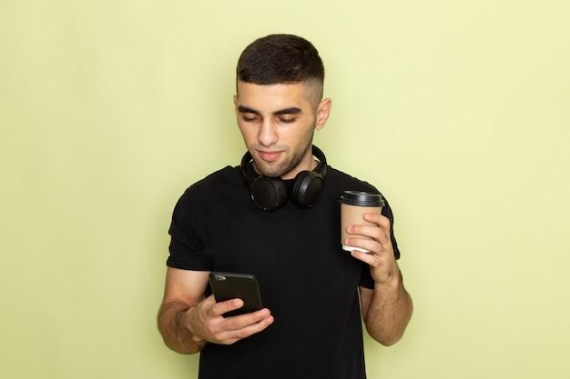 Вид спереди молодой самец в черной футболке держит телефон и слушает музыку, держа чашку кофе на зеленом