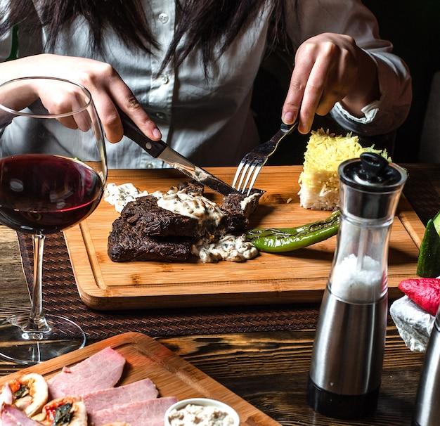 木の板にご飯とソースの下で揚げステーキ