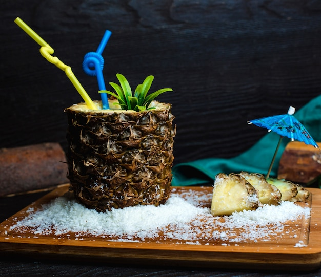 Ананас свежий на деревянной доске с кокосом