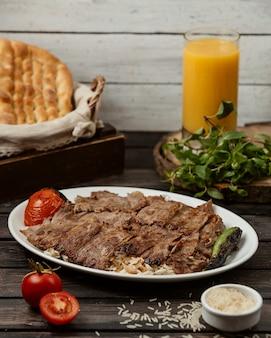 Кебаб из ломтиков говядины с рисом, подается с жареными помидорами и перцем