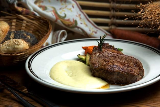 Хорошо приготовленный стейк с картофельным пюре и жареными овощами