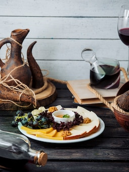 Сырная тарелка с чеддером, копченым, белым сыром, грецким орехом, виноградом и медом