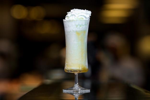 長いグラスにホイップクリームとオレンジミルクセーキ
