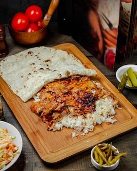 木の板にご飯と鶏のドナー