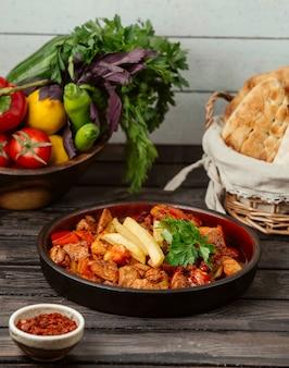 Кусочки жареной курицы, приготовленные с помидорами, перцем и картофелем фри