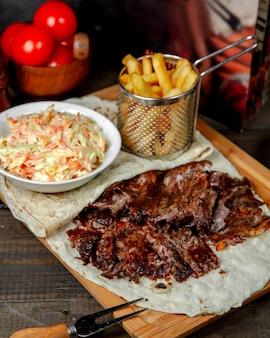 Мясо донер с картофелем фри на деревянной доске