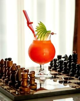 Фруктовый коктейль, украшенный кусочками яблок на шахматной доске