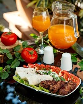 Тарелка с люля-кебабом с помидорами, сладким перцем, лепешками и луком