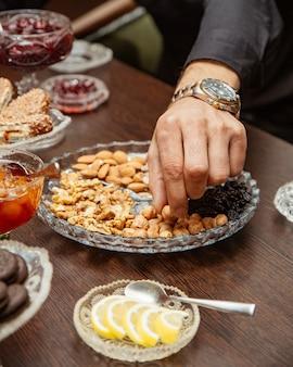 Человек принимает фундук из орехового блюда