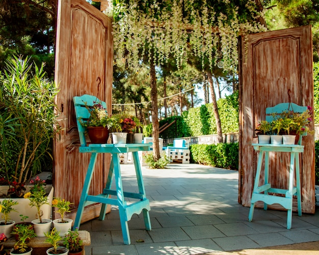 Вход в ресторан с деревянными дверями и двумя бирюзовыми стульями с растением