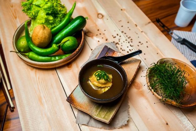 Тарелка японского супа с клецками, тарелка с овощами и фруктами и миска с травами