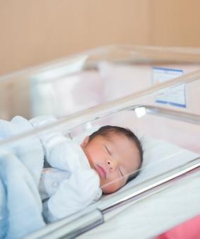 生まれたばかりの赤ちゃんは、新生児服で病院のベビーベッドで眠る