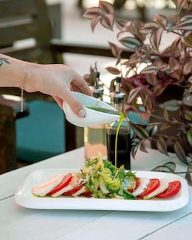 Человек наливает соус на салат
