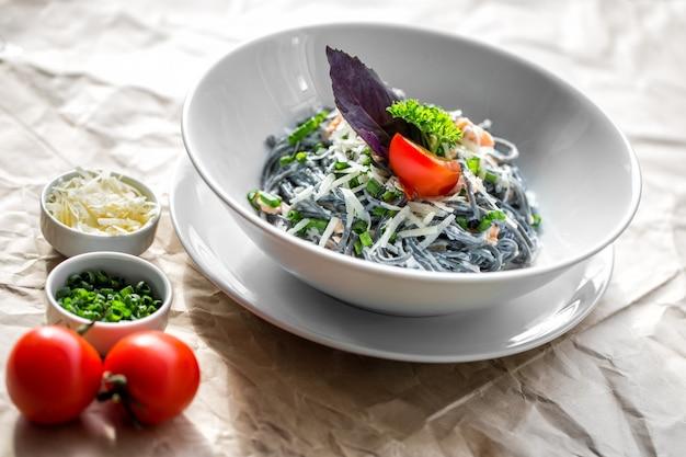 Черная паста в соусе с зеленым луком и помидором