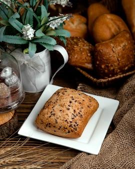 Булочка из черного хлеба с кунжутом и семенами льна на вершине