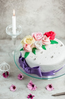 クリーム色のバラで飾られたケーキ_