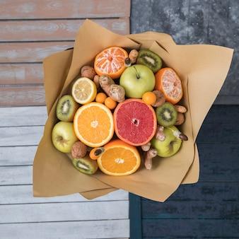 Вид сверху на букет из фруктов и орехов, завернутый в крафт-бумагу