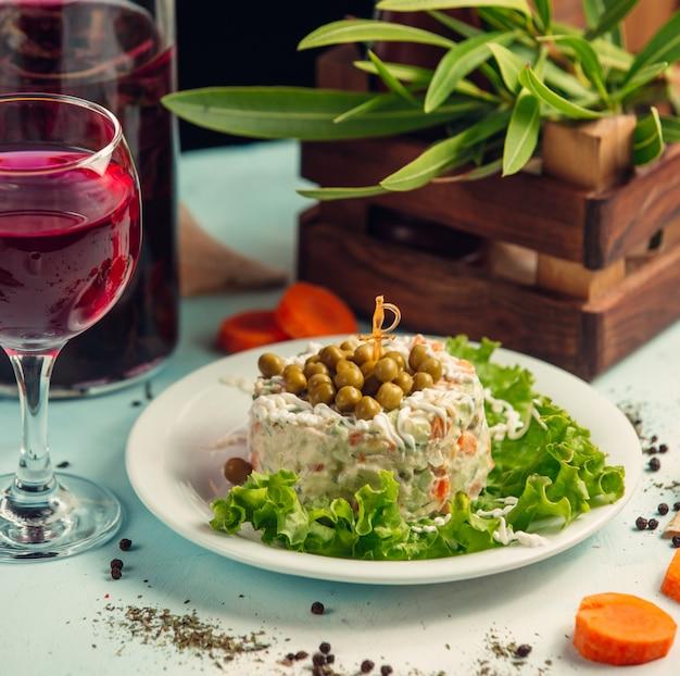 Столичный салат с красным вином на столе