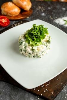 Салат майонезный с листьями салата на белой тарелке