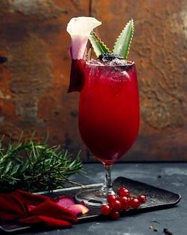 Стакан красного напитка со льдом и листьями алоэ