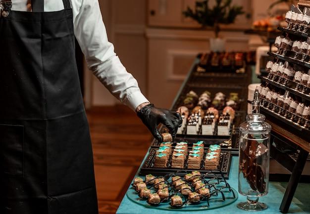 Официант накрывает банкетный стол со сладостями