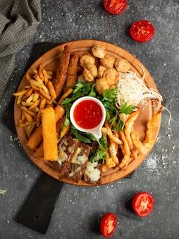 Деревянный поднос с картофелем, сырными палочками и жареными гренками