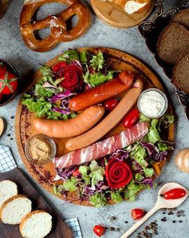 Смешанные колбаски на столе с бубликом