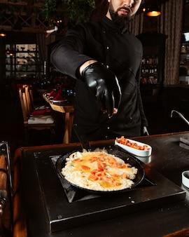 Кук капает нарезанный помидор в яичницу