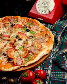 ソーセージ、トマト、ピーマン、オリーブのピザ