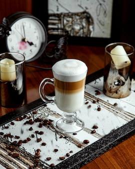 テーブルの上のラテとコーヒー豆とガラス