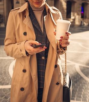 電話と噴水広場でコーヒーを持つ女性