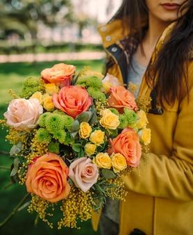 オレンジ、黄色のバラ、ミモザと秋の花の花束を持つ女性