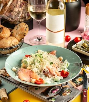 Тарелка салата цезарь с копченым лососем, украшенная тертым пармезаном